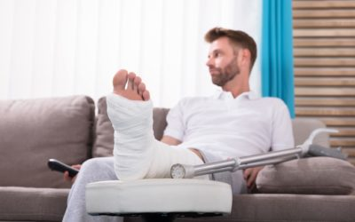 Young Man With Broken Leg Sitting On Sofa Holding Remote